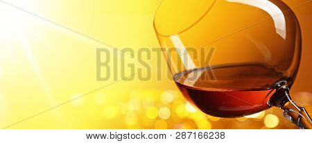 Snifter Of Brandy On A Yellow Background. Copy Space For Text.