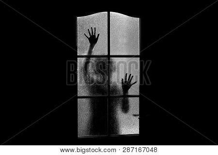 Dark Silhouette Of Girl Behind Glass. Locked Alone In Room Behind Door On Halloween In Grayscale. Ni