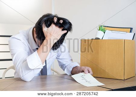 Businessmen are holding resignation document and packing personal company on brown cardboard box changing work, unemployment or resign concept. poster
