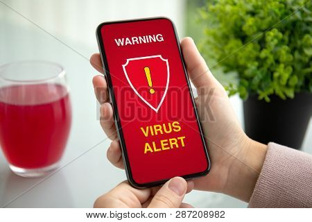 Female Hands Holding Phone With Warning Virus Alert Alarm On Screen In Summer Cafe