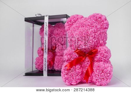 Pink Teddy Bear Toy Of Foamirane Roses. The Same Teddy In Clear Box With Black Paper Cover On Backgr