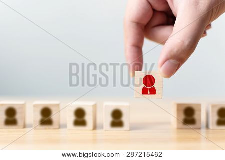 Hand Of A Businessman Chooses A Wooden Cube Block With Icon People Standing Out From The Crowd. Succ