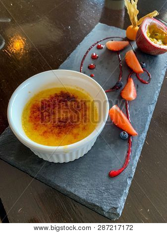 Creme Brulee On Black Ceramic Plate With Fresh Fruits