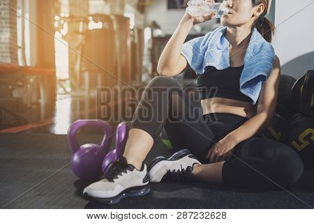 Sport Woman Sitting And Resting After Workout Or Exercise In Fitness Gym With Protein Shake Or Drink
