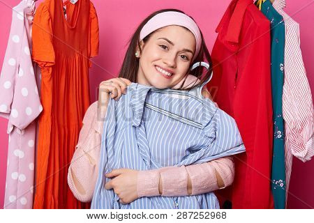 Happy Smiling Woman Chooses Blouse. Satisfied Lady Likes Purchase. Brunette Embraces Hanger With Blu