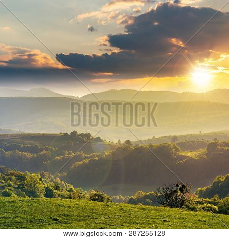 Green Rolling Hills Of Romania Countryside At Sunset. Agricultural Field With Green Grass. Mountain