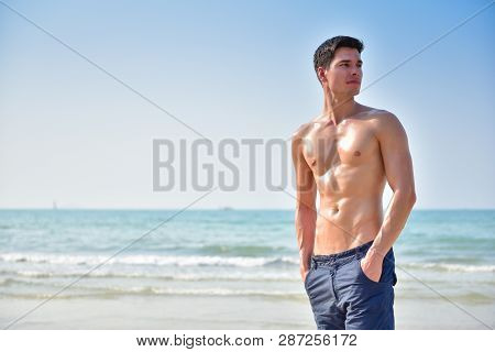 Handsome Young Man With Nude Torso Standing And Looking Sideways Over Beach Background. Copy Space.