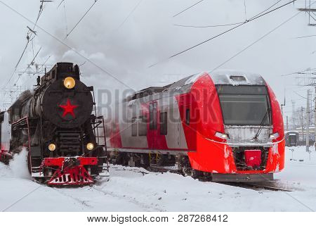 Steam Locomotive And Modern Electric Multiple-unit Train Stand Nearby At Station In Winter