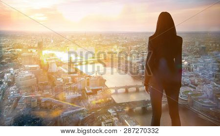Young Woman Looking Over The City Of London At Sun Set. Future, New Business Opportunity And Busines