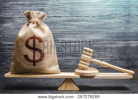 Bag Of Money With A Dollar Sign And A Judge's Hammer On The Scales. Concept Lobbying For The Adoptio