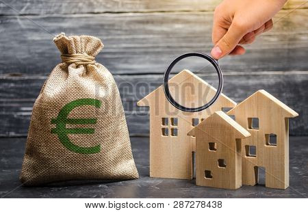 Magnifying Glass Is Looking At A Bag With Euro Money And Three Houses. Affordable Cheap Loan, Mortga