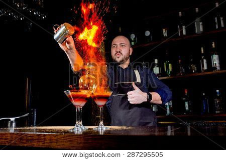 Fiery Show At The Bar. The Bartender Makes Hot Alcoholic Cocktail And Ignites Bar. Bartender Prepare