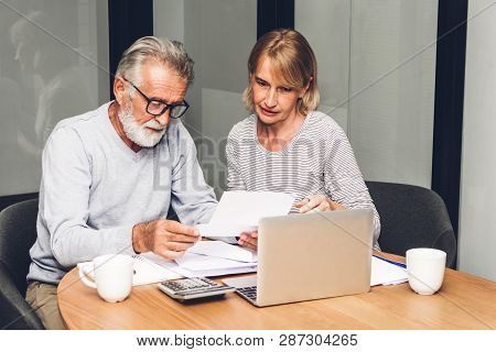 Senior Couple Reading Documents And Calculating Bills To Pay In Living Room At Home.retirement Coupl