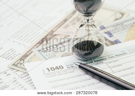 Tax Time In April Concept, Pen On 1040 Us Individual Income Tax Filling Form With Sandglass Or Hourg