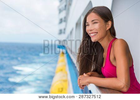 Happy Asian travel tourist woman relaxing on cruise ship deck enjoying summer Europe destination vacation cruising on sea.