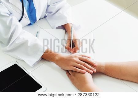 Woman Doctor And Female Patient In Hospital Office