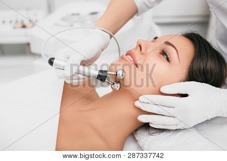 Beautiful woman receiving facial microcurrent procedure for rejuvenation skin. poster