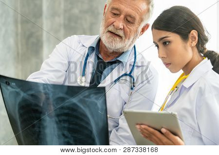 Doctors Working With X Ray Film Of Patient Chest.