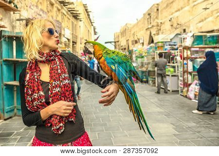 Happy Woman Kisses A Parrot At Bird Souq Inside Souq Waqif, The Old Market And Tourist Attraction In