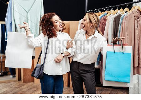 Mother And Daughter Feeling Happy And Satisfied While Leaving Shop With Bags