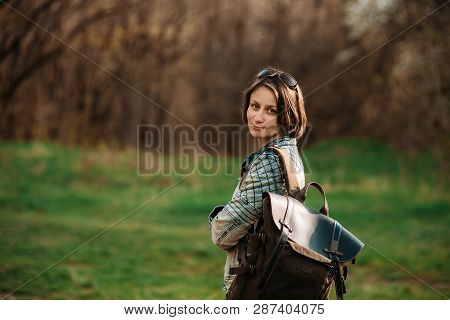 Photo Of Happy Hiking Middle-aged Woman In Blue Jacket With Backpack Resting In Evening Spring Fores