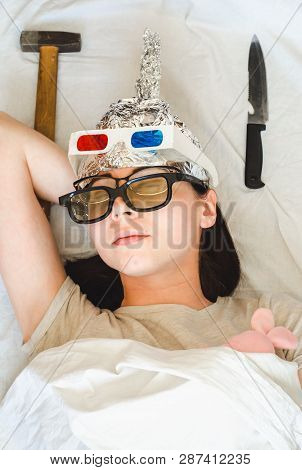 Paranoid woman sleeps with different kinds of protection including foil hat, glasses and weapons against fears, aliens, special services poster