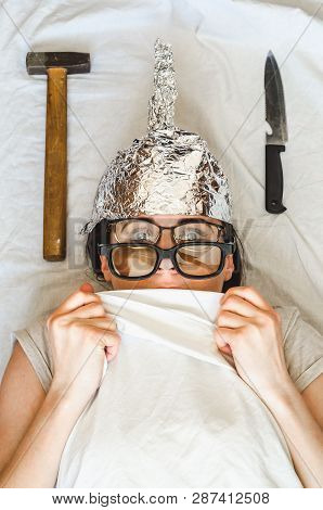 Frightened paranoid woman wears foil helmet and sleeps with weapon and different glasses because of mental illness. Concept of schizophrenia, phobias and anxiety poster