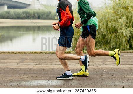 Two Elderly Men Runners Run Marathon Along Embankment Of River