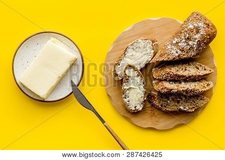 Wholegrain Bread On Cutting Board With Butter On Plate, Slice Of Bread With Butter On Yellow Backgro