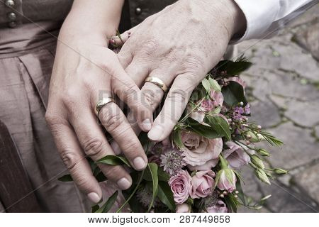 Hands Of Bride And Groom With Flower Bouquet
