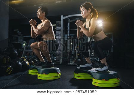 Group Of Healthy Fitness People In Gym, Young Couple Is Working Out At Gym, Attractive Woman And Han