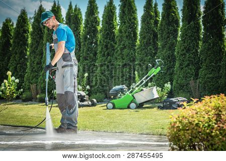 Caucasian Men In His 30s Cleaning Garden Paths And Driveway Using Professional Pressure Washer. Gard