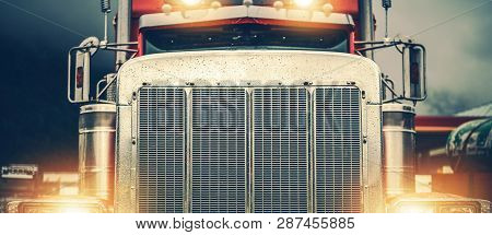 Shiny American Semi Truck On A Road. Large Chromed Grill Front View In Wide Format. Trucker On The R