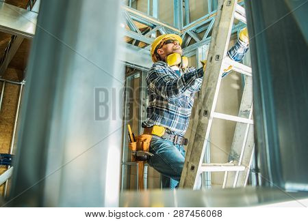 Skeleton Steel Building Construction Worker Wearing Safety Hard Hat And Noise Reduction Headphones.