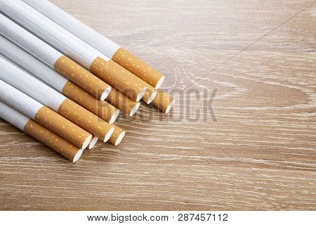 Several Cigarettes On A Brown Wooden Background