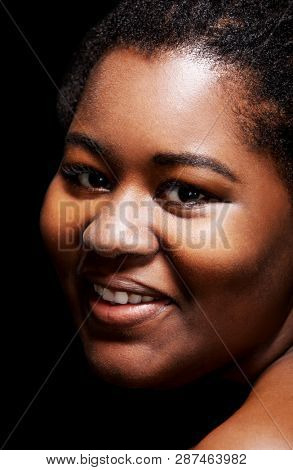 Natural looking african woman with smile on face looking to camera.