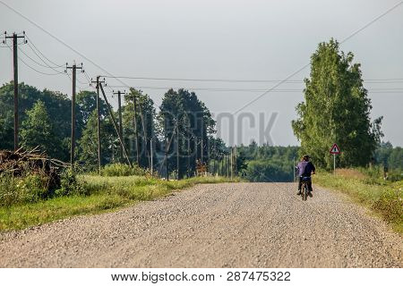 Summer Landscape With Road, Trees And Blue Sky. Man Ride To The Moped On Countryside Road. Rural Roa