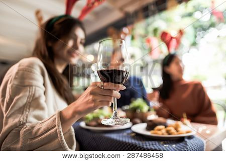Dinner With Friends. Group Of Young People Enjoying Dinner Together. Focus On A Glass Of Wine.