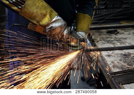 Grinding. The Man Polishes Metal Rods. Workshop. The Worker Polishes The Metal.