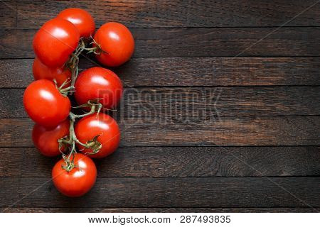 Tomatoes On Dark Oak Table With Copy Space