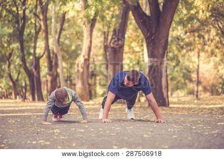 Little Boy And His Father Exercising Together In The Park. Father And Son Spend Time Together And Le