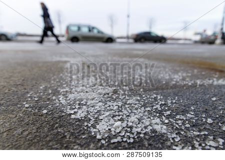 De-icing Chemicals On The Road. Pavement Is Sprinkled With Technical Salt Or Salt Mixtures Based On