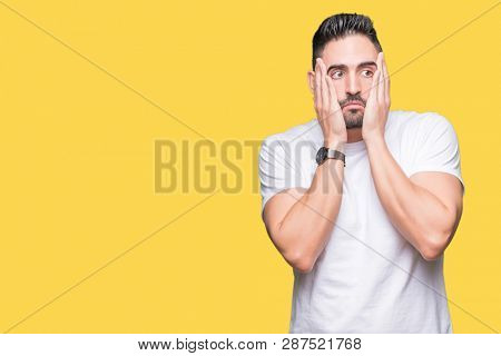 Handsome man wearing white t-shirt over yellow isolated background Tired hands covering face, depression and sadness, upset and irritated for problem