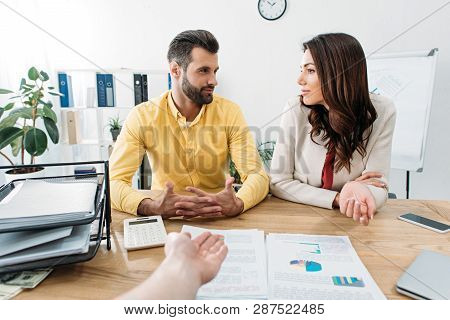 Investors Sitting At Table And Talking Wile Advisor Pointing At Documents With Hand In Office