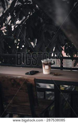 Abstract Scene Of Iced Latte In Plastic Coffee Cup With Blank White Label And Smartphone On Wood Bar