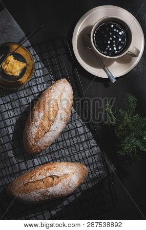 Top View Of Baguette, European Style Bread With Margarine And Black Coffee On Black Wood Table In Ea