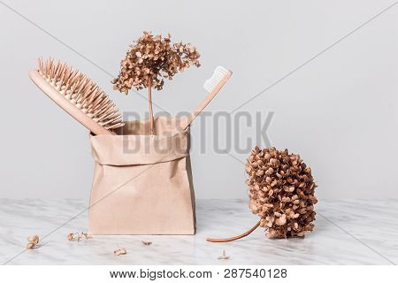 Hairbrush, Toothbrush And Dried Gardenias Stored In A Natural Paper Bag.