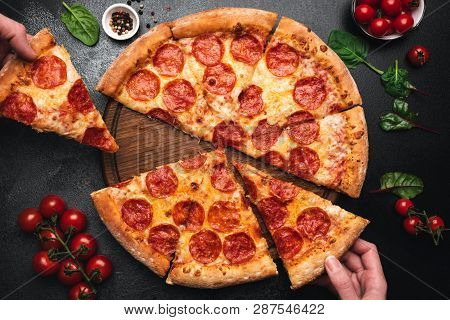 Picking Slice Of Pepperoni Pizza. Hands Picking Pizza Slice. Top View Of Tasty Hot Pepperoni Pizza O