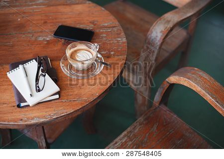 Abstract Scene Of Coffee Cup, Notebooks,and Mobile Phone On Rustic Wood Table. Coffee Break And Rela