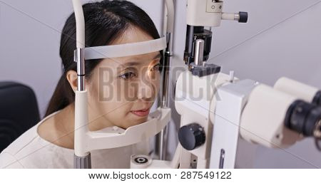 Asian Woman do eye test at clinic